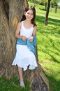 Happy young girl pretty leaning against a tree in a white dress outside in a park american venezuelan Stock Photo