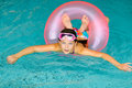 Happy young girl relaxing in pink life preserver in a swimming pool wearing pink goggles