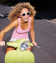 Happy young girl riding a scooter on road Royalty Free Stock Photography