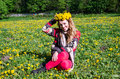Happy young girl sitting in the park on a field of grass and dandelions with a bouquet of dandelions on his head and smiling