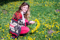 Happy young girl sitting in the park on a field of grass and dandelions and picking flowers to make a bouquet