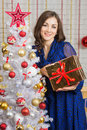 Happy young girl standing with a gift from the Christmas trees Royalty Free Stock Photo