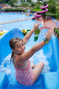 Happy young girl on tropical water slide child in swimming pool Royalty Free Stock Image