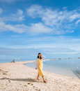 Happy young girl walks on long narrow beach single looks at the camera when walking curving stretch of white sand during low tides Stock Image