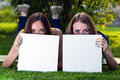 Happy young girls holding white blank papers against background of summer green park showing boards female Stock Photography