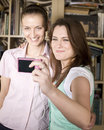 Happy young girls making funny face while taking pictures stock photo of themselves through cellphone Royalty Free Stock Photos