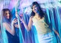 Happy young girls at night club with drinks dancing Royalty Free Stock Photography