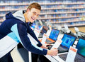 Happy young guy in consumer electronic shop Stock Photography