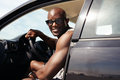 Happy young guy in his car portrait of looking at camera smiling african male model wearing sunglasses muscular man on road trip Stock Photography