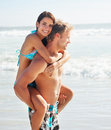 Happy young guy piggybacking his girlfriend Royalty Free Stock Photos