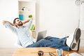 Happy young guy is relaxing at work Royalty Free Stock Photo