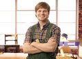 Happy young handyman in workshop carpenter smiling Stock Image