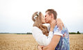 Happy young hippie couple kissing in field Royalty Free Stock Photo