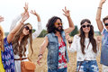 Happy young hippie friends dancing on cereal field nature summer youth culture and people concept Royalty Free Stock Image