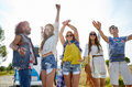 Happy young hippie friends dancing outdoors nature summer youth culture and people concept over minivan car Stock Photography