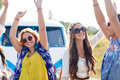 Happy young hippie friends dancing outdoors nature summer youth culture and people concept over minivan car Royalty Free Stock Images