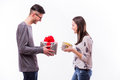 Happy young hipster couple change with present each other isolated on a white background holiday Royalty Free Stock Photo