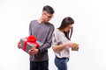 Happy young hipster couple change with present each other isolated on a white background holiday Royalty Free Stock Photos