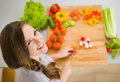 Happy young housewife cutting fresh vegetables in kitchen Royalty Free Stock Images