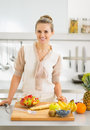 Happy young housewife cutting fruits in kitchen modern Royalty Free Stock Photo