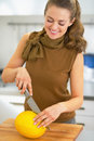 Happy young housewife cutting melon in kitchen Stock Photo