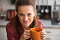Happy young housewife drinking tea in kitchen Royalty Free Stock Photo