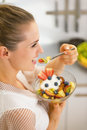 Happy young housewife eating fresh fruit salad rear view in kitchen Stock Photography