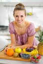 Happy young housewife with fruits on cutting board in modern kitchen Stock Image