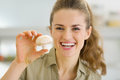 Happy young housewife holding mushroom in kitchen Royalty Free Stock Image