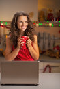 Happy young housewife with laptop and cup of hot chocolate in kitchen Royalty Free Stock Images