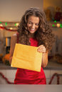 Happy young housewife opening package in kitchen christmas decorated Royalty Free Stock Image