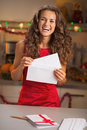 Happy young housewife putting christmas letter into envelope in red dress Stock Images