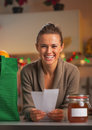 Happy young housewife with receipts from christmas purchases in kitchen Royalty Free Stock Photo