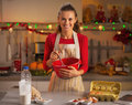 Happy young housewife whisking dough in kitchen christmas decorated Royalty Free Stock Image