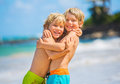 Happy young kids playing at the beach on summer vacation siblings and best friends concept Stock Image