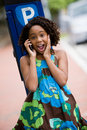 Happy young lady on cellphone african ethnicity girl talking surprised Royalty Free Stock Photos
