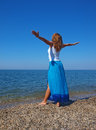 Happy young lady standing on a coastline with hands out stretched Royalty Free Stock Photos