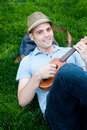 Happy young male student on campus with ukulele Royalty Free Stock Images