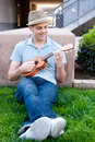 Happy young male student on campus with ukulele Royalty Free Stock Photos