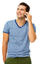 Happy young man answering smart phone while standing against white background vertical shot Stock Photography