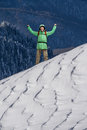 Happy young Man with backpack standing on snowy mountain slope. Alpinist or mountain hiker.