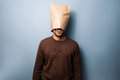 Happy young man with a bag over his head standing Stock Images