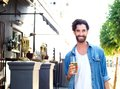 Happy young man in blue shirt holding glass of beer outdoors portrait a at an outdoor bar Stock Images