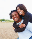 Happy young man carrying a woman on his back Royalty Free Stock Photos