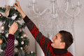 Happy young man decorating a christmas tree smiling as he stretches to place the ornament on top Royalty Free Stock Images