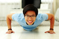 Happy young man doing push ups portrait of a in the living room at home Stock Photos