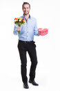Happy young man with flowers a gift. Royalty Free Stock Photography