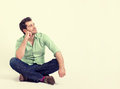 Happy young man in green shirt and blue jeans sitting on the floor Royalty Free Stock Photo