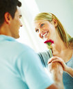 Happy young man handing a flower  to a young woman Royalty Free Stock Photography