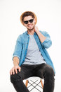 Happy young man in hat and sunglasses sitting on chair Royalty Free Stock Photo